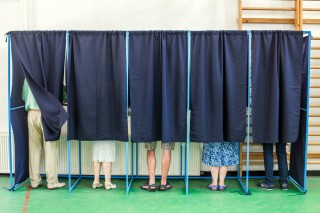 Image of voting booths via Shutterstock