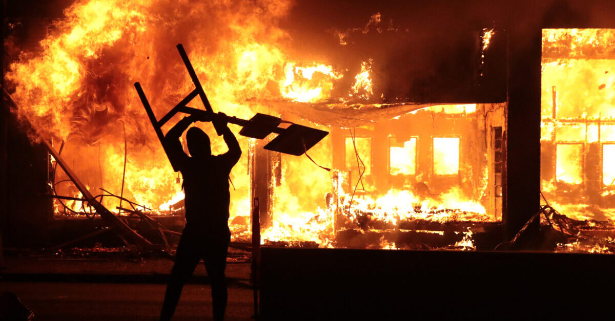 MINNEAPOLIS, MINNESOTA - MAY 29: A man holds up a sign near a burning building during protests sparked by the death of George Floyd while in police custody on May 29, 2020 in Minneapolis, Minnesota. Earlier today, former Minneapolis police officer Derek Chauvin was taken into custody for Floyd's death. Chauvin has been accused of kneeling on Floyd's neck as he pleaded with him about not being able to breathe. Floyd was pronounced dead a short while later. Chauvin and 3 other officers, who were involved in the arrest, were fired from the police department after a video of the arrest was circulated.