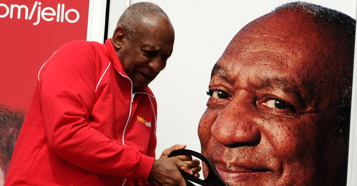 Bill Cosby appears in front of a photo of his face