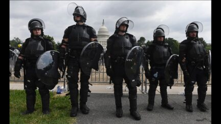 Police stand guard as demonstrators gather for the