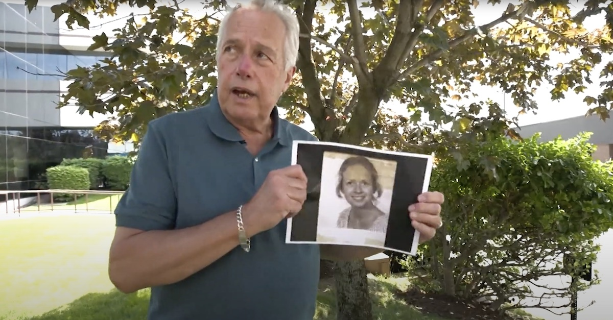 Jim McCormack holding a photo of his sister Kathie