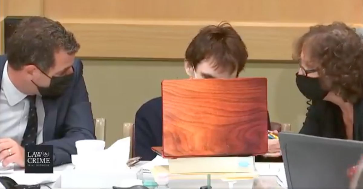 Earlier in the hearing, a woman wearing a black face mask (R) passed a bundle of colored pencils toward Nikolas Cruz (C).
