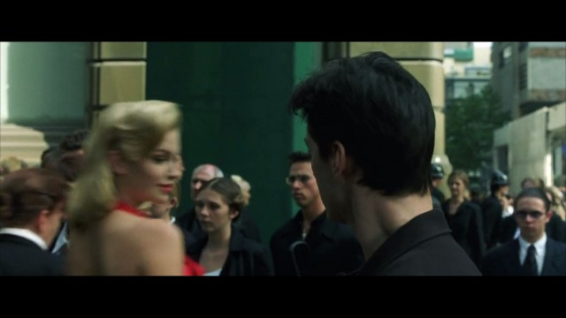 Neo sees the woman in the red dress.