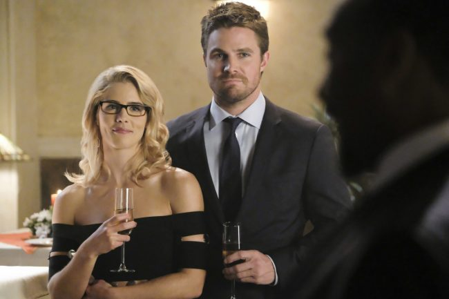 """image: Bettina Strauss/The CW Supergirl -- """"Crisis on Earth-X, Part 1"""" -- Pictured (L-R): Emily Bett Rickards as Felicity Smoak and Stephen Amell as Oliver Queen -© 2017 The CW Network, LLC. All Rights Reserved"""