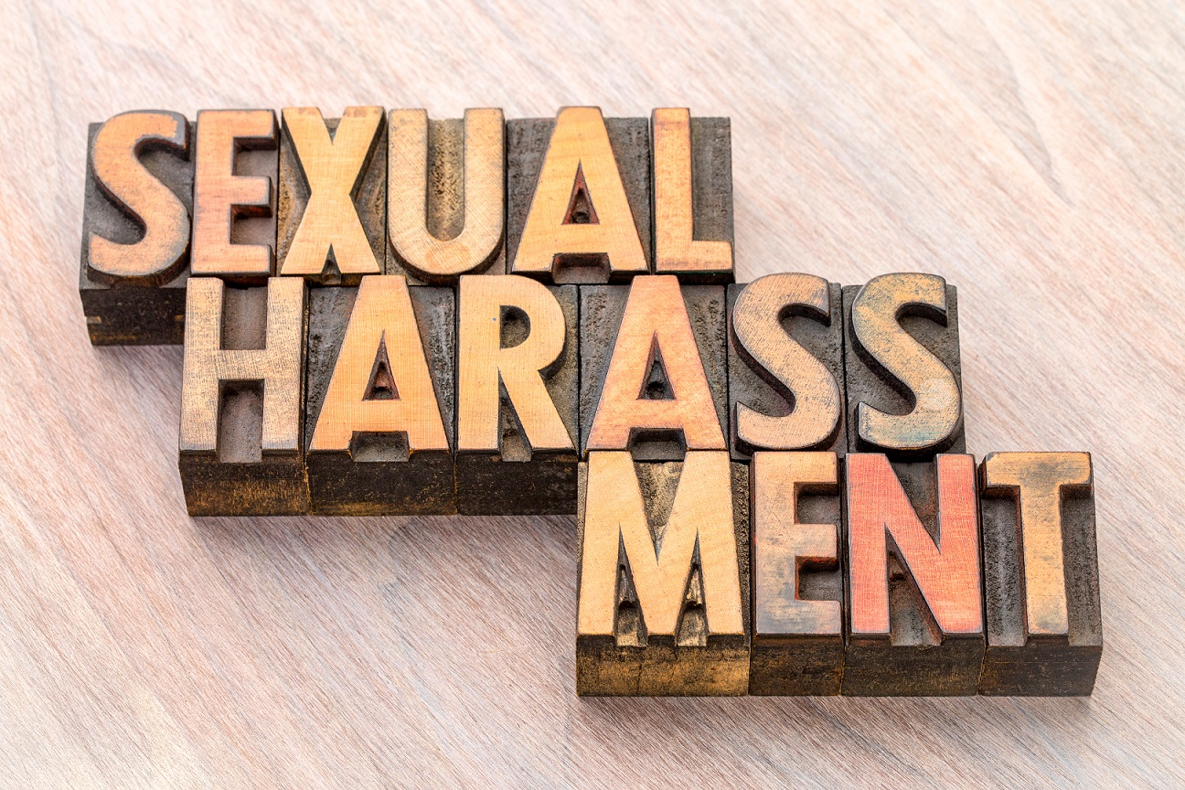 Shutterstock image of the words sexual harassment in wood-block letters
