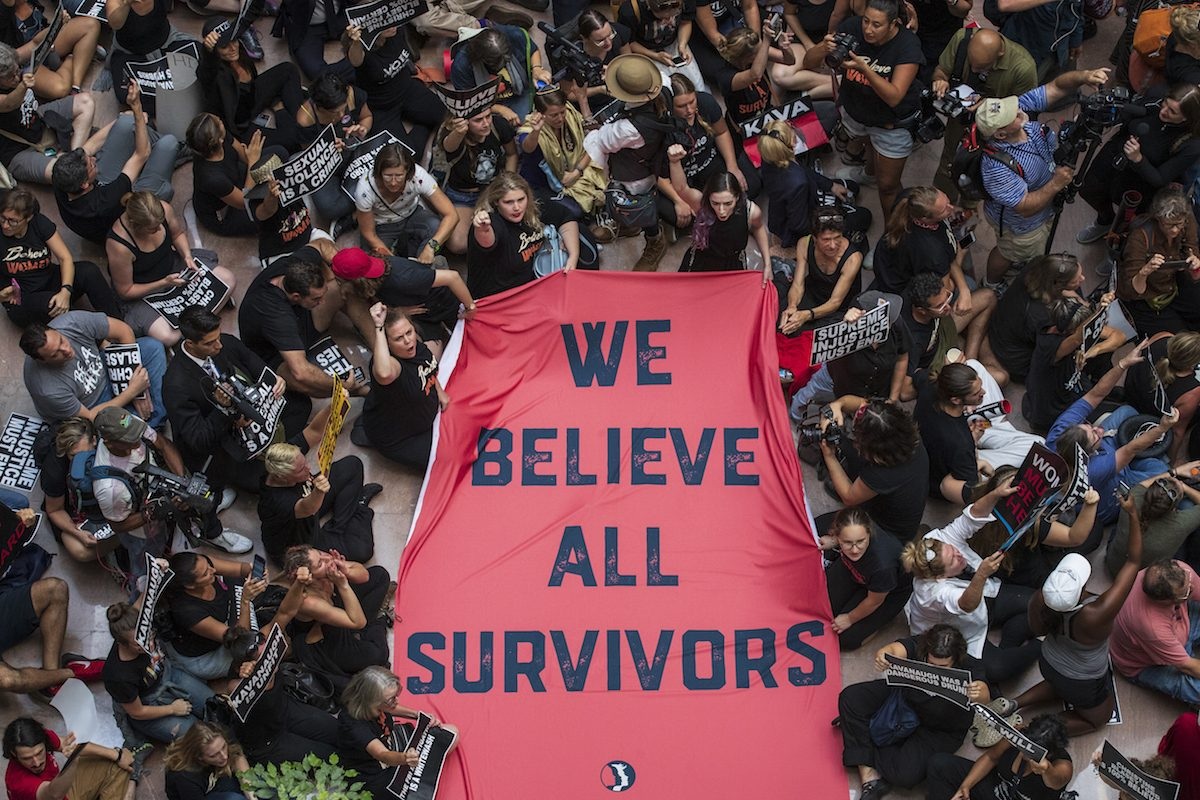 A crowd of people protesting Brett Kavanaugh's confirmation hold a sign reading 'We believe all survivors'