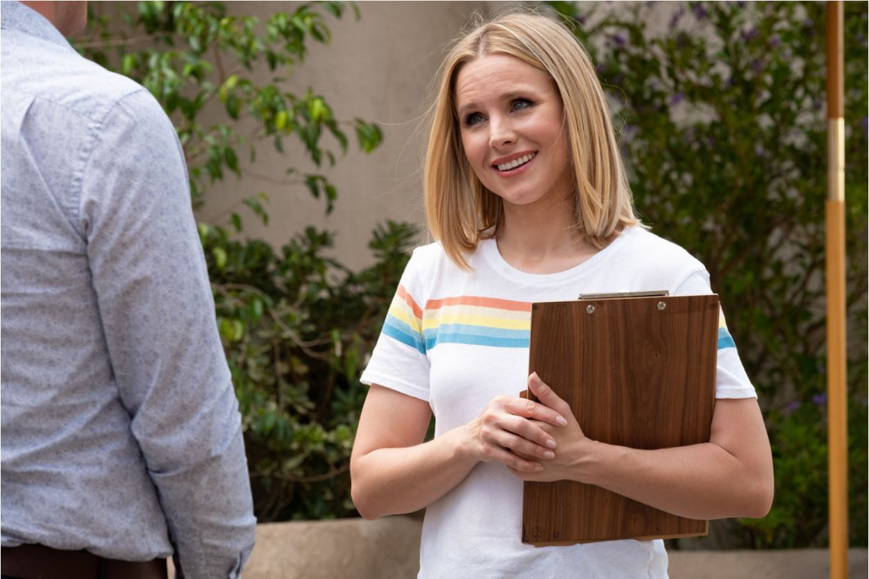 Eleanor Shellstrop (Kristen Bell) stands smiling with a clipboard in NBC's The Good Place.