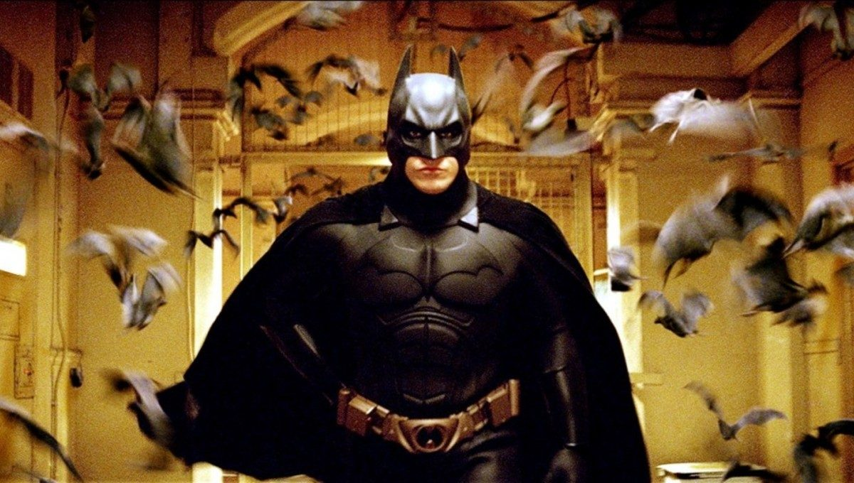 Christian Bale, flocked by bats, in Batman Begins.