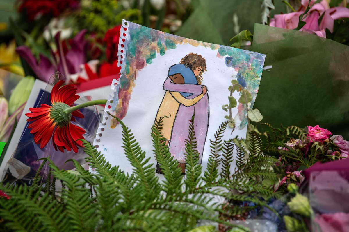 A picture is left among flowers and tributes near Al Noor mosque on March 18, 2019 in Christchurch, New Zealand
