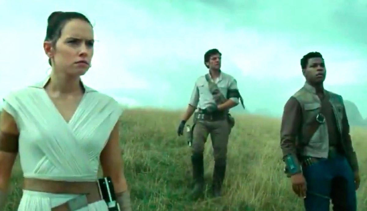 The Star Wars sequel trilogy trio stands on a hill overlooking a destroyed Death Star.