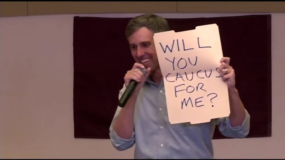 """Beto O'Rourke holds up a sign asking a girl in the audience """"Will you caucus for me?"""""""