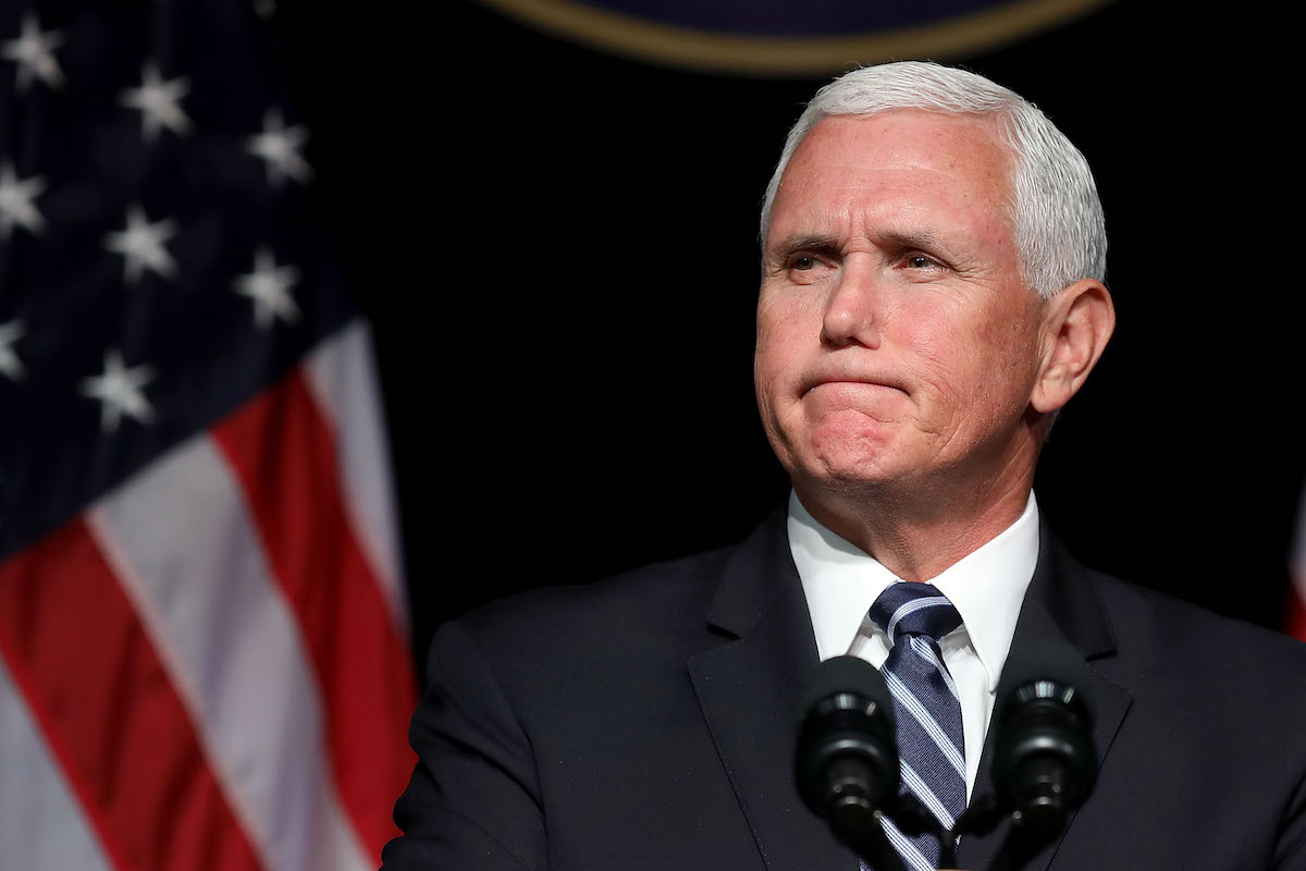 Mike Pence looks unhappy in front of the American flag.