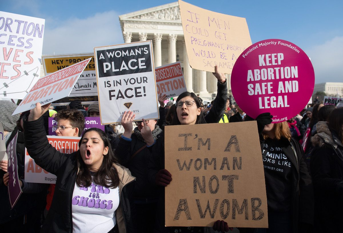 Pro-choice activists holding signs at a rally.