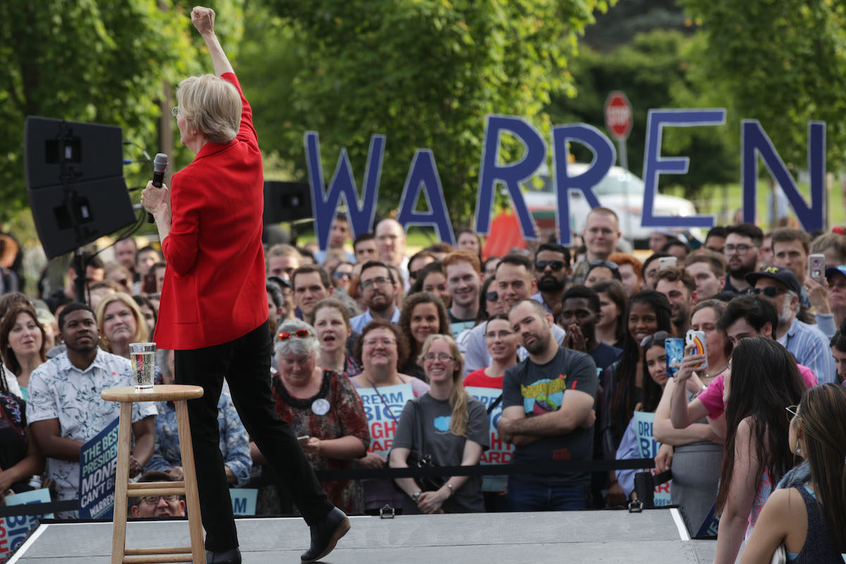 Elizabeth Warren onstage at a rally with supporters in front of her.