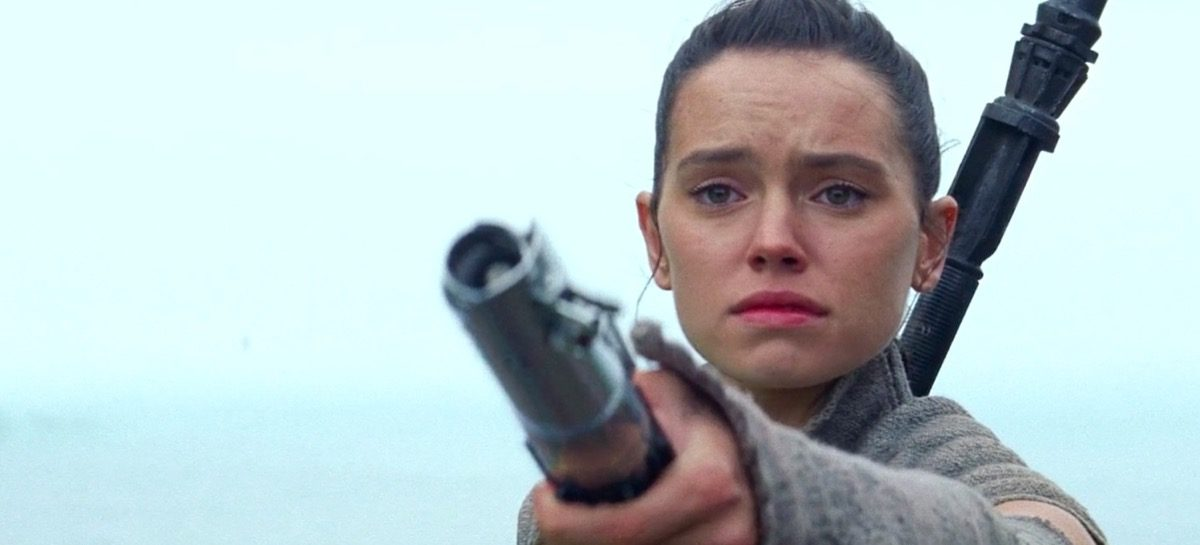 Rey holding Anakin's lightsaber out to Luke Skywalker at the end of Star Wars: The Force Awakens.