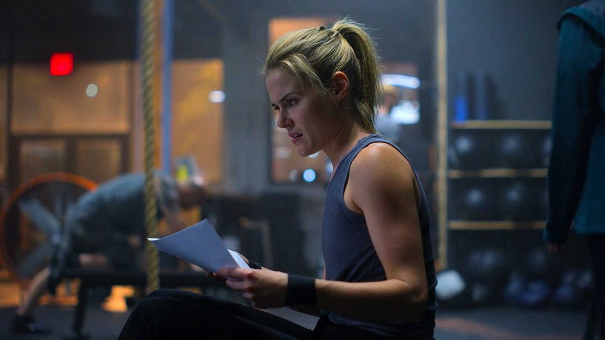 Trish sitting in the gym, holding a piece of paper in Marvel and Netflix's Jessica Jones season 3.