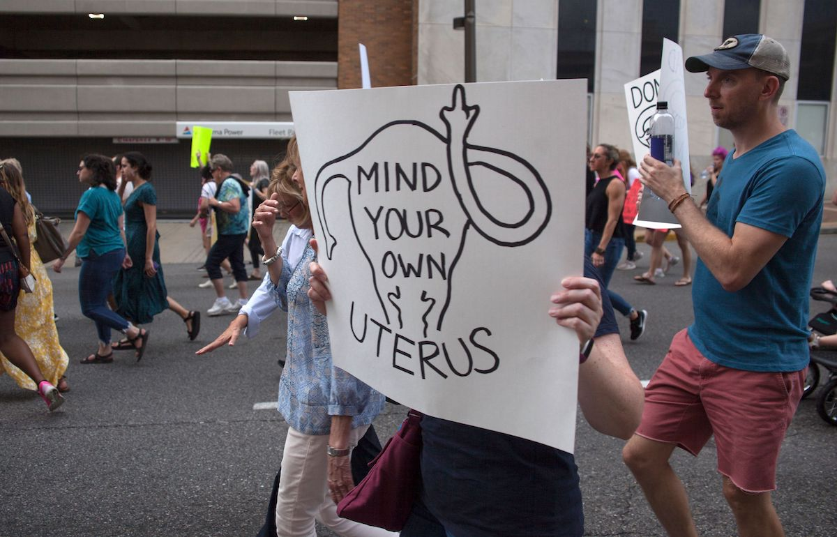 Pro-Abortion protest sign reading 'mind your own uterus'