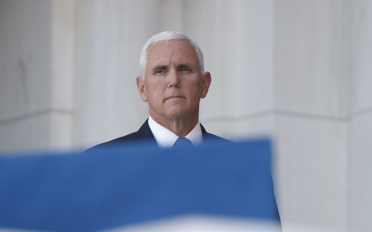 Mike Pence peeks out from behind a flag with an expression that screams 'soon.'