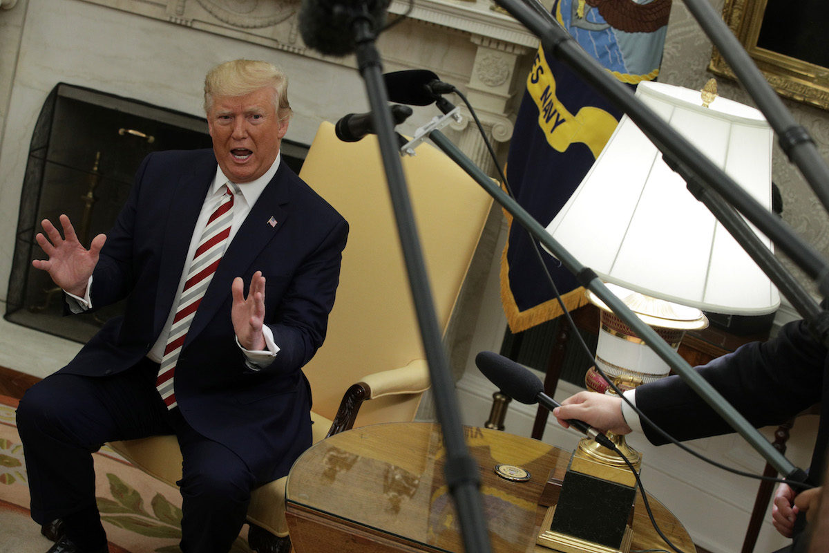 Donald Trump rants in the Oval Office, surrounded by reporters' microphones.
