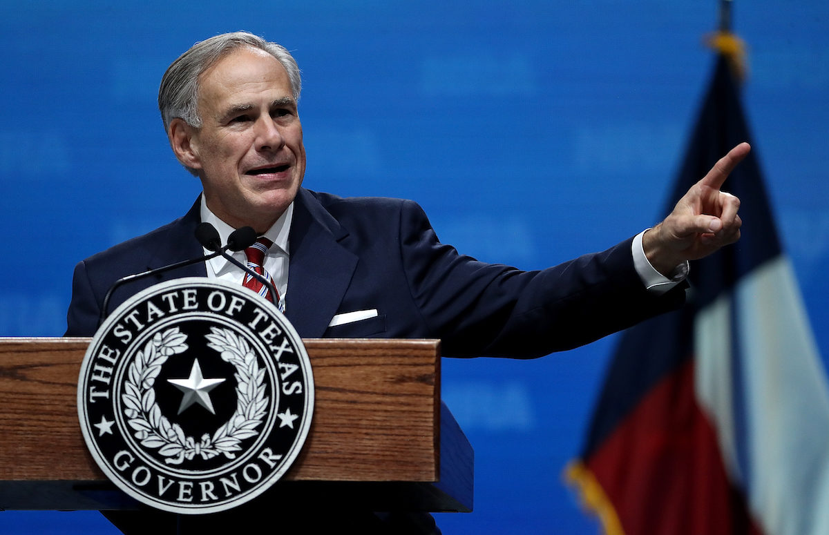Texas Governor Greg Abbott speaks from a podium at an NRA convention.