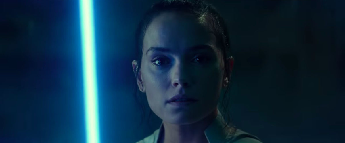 Rey stares into the camera, holding up a blue lightsaber in Star Wars: The Rise of Skywalker trailer.