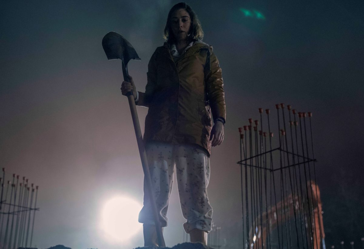 Annie Wilkes stands with a shovel looking into the pit