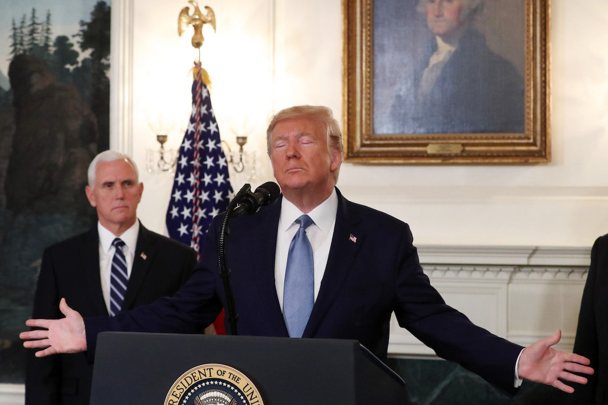 Trump makes Jesus arms as Mike Pence looks on in front of George Washington's portrait.