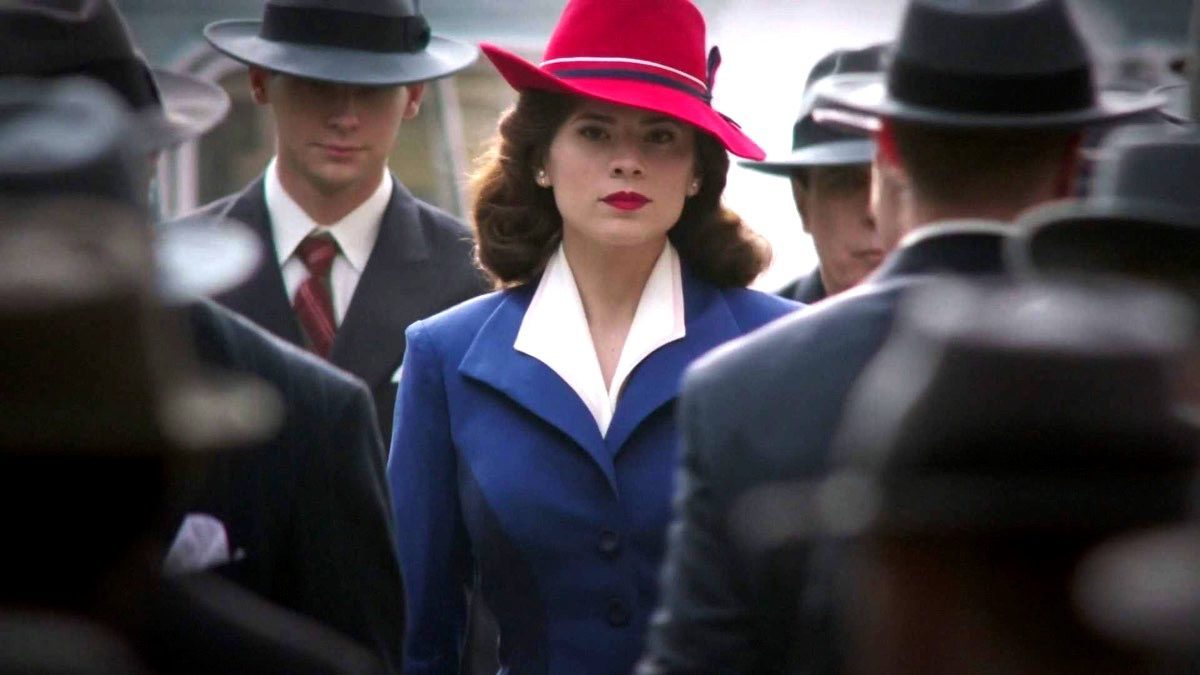 Peggy Carter in her colorful outfit, walking in a crowd of grey suits in Marvel's Agent Carter.