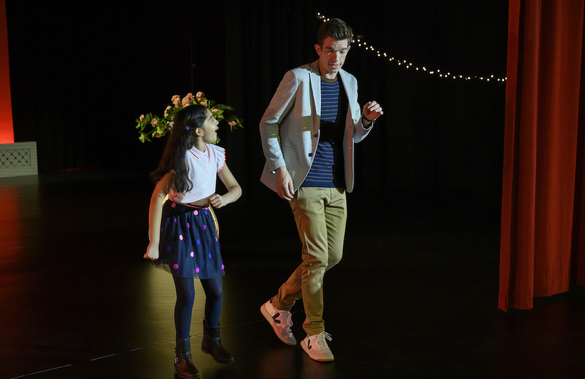 John Mulaney and a young girl dance on a stage.