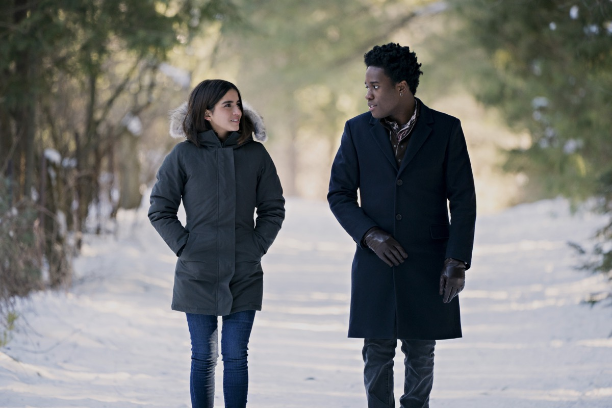 Isabela Merced, Shameik Moore walk together through the snow in Netflix's Let It Snow.