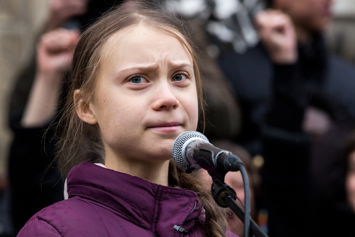 Greta Thunberg stands at a microphone and frowns.
