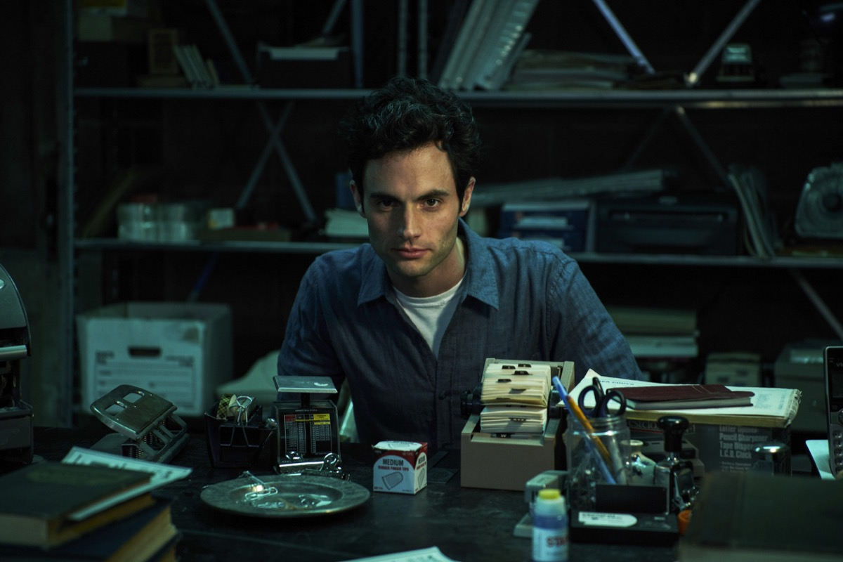 Penn Badgley as Joe, sitting behind his basement desk in Netflix's You.