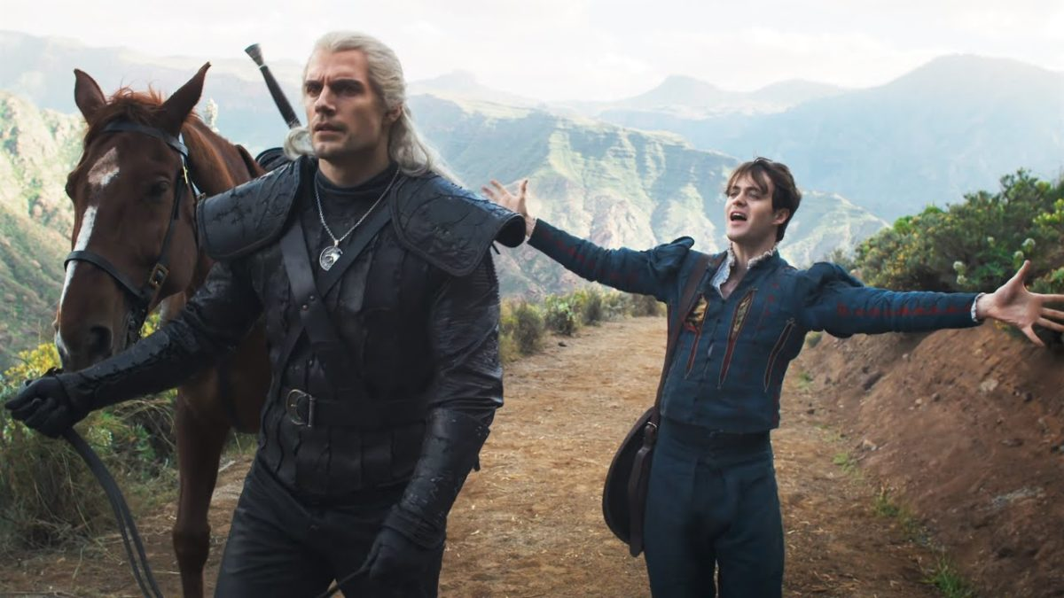 Geralt walks along with his horse while Jaskier gestures enthusiastically with arms wide in Netflix's The Witcher.