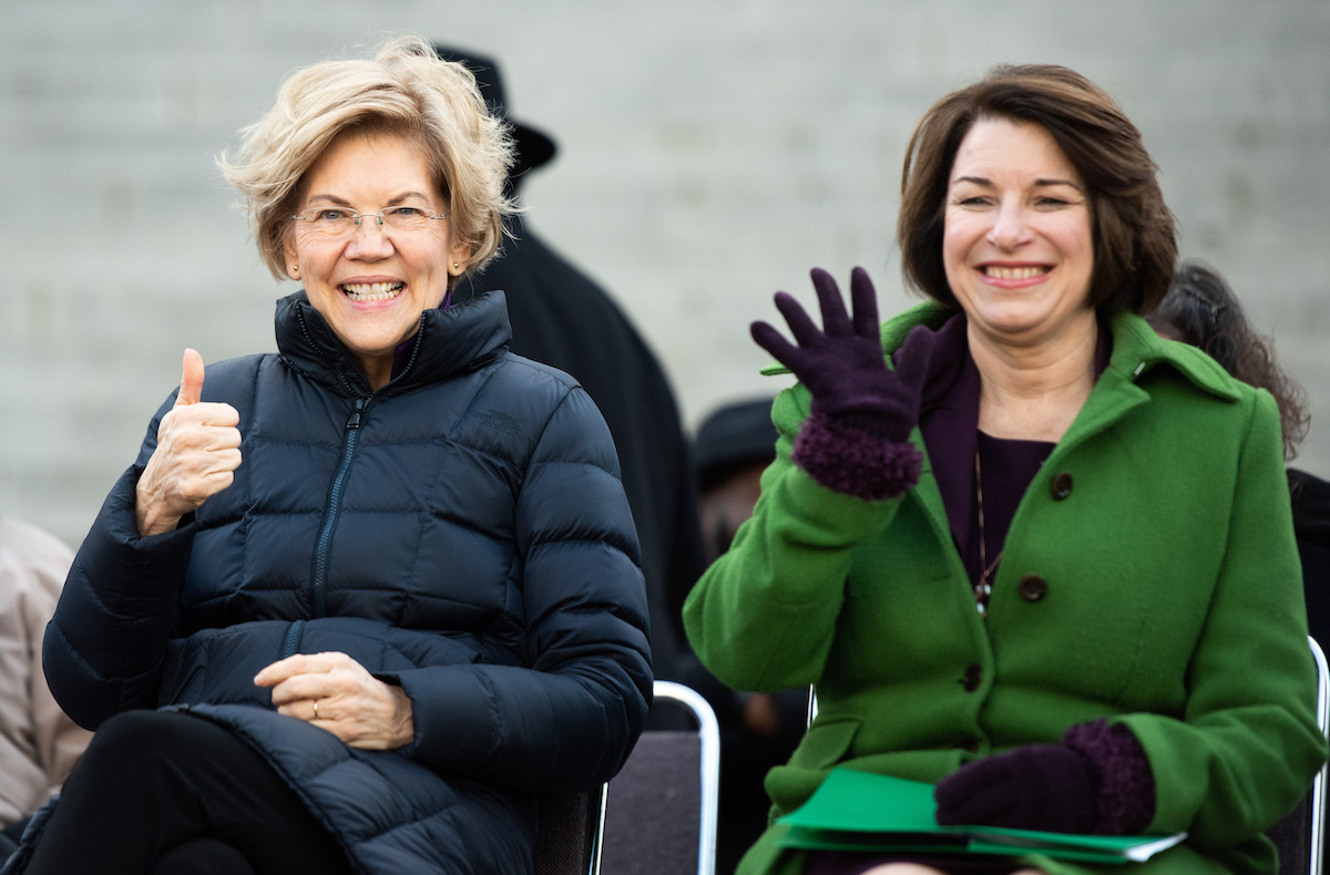 Democratic presidential candidates, Sen. Elizabeth Warren (D-MA), left, and Sen. Amy Klobuchar (D-MN) gesture to the crowd during the King Day at the Dome rally