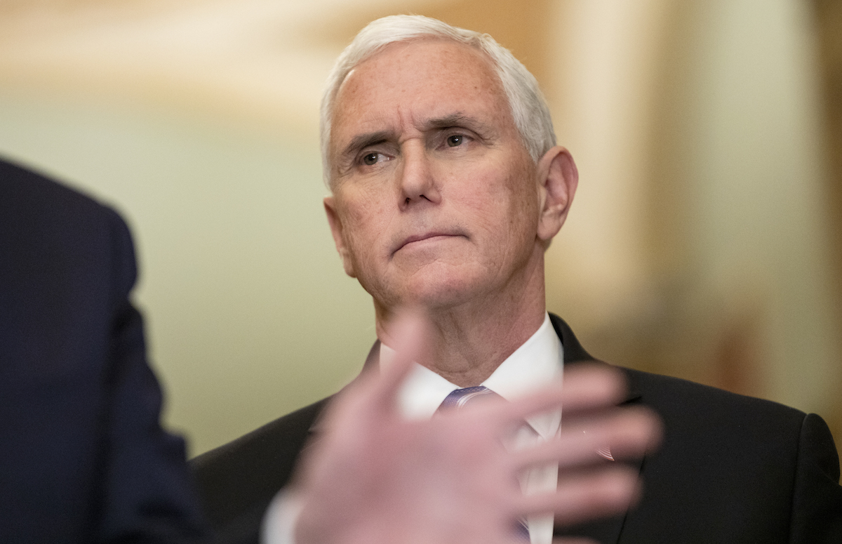 Vice President Mike Pence listens and looks on disapprovingly as Donald Trump talks to reporters