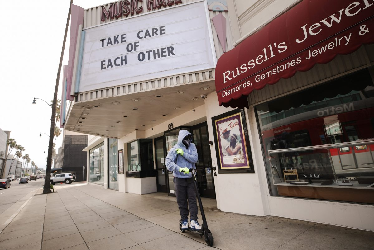 BEVERLY HILLS, CALIFORNIA - MARCH 18: A man wears gloves and a bandanna across his face while riding a scooter past a shuttered movie theater, with the message 'Take Care of Each Other' displayed on the marquee, on March 18, 2020 in Beverly Hills, California. The city of Beverly Hills mandated the closure of 'non-essential' stores, including the famous retailers on Rodeo Drive, starting today in response to the COVID-19 pandemic. (Photo by Mario Tama/Getty Images)