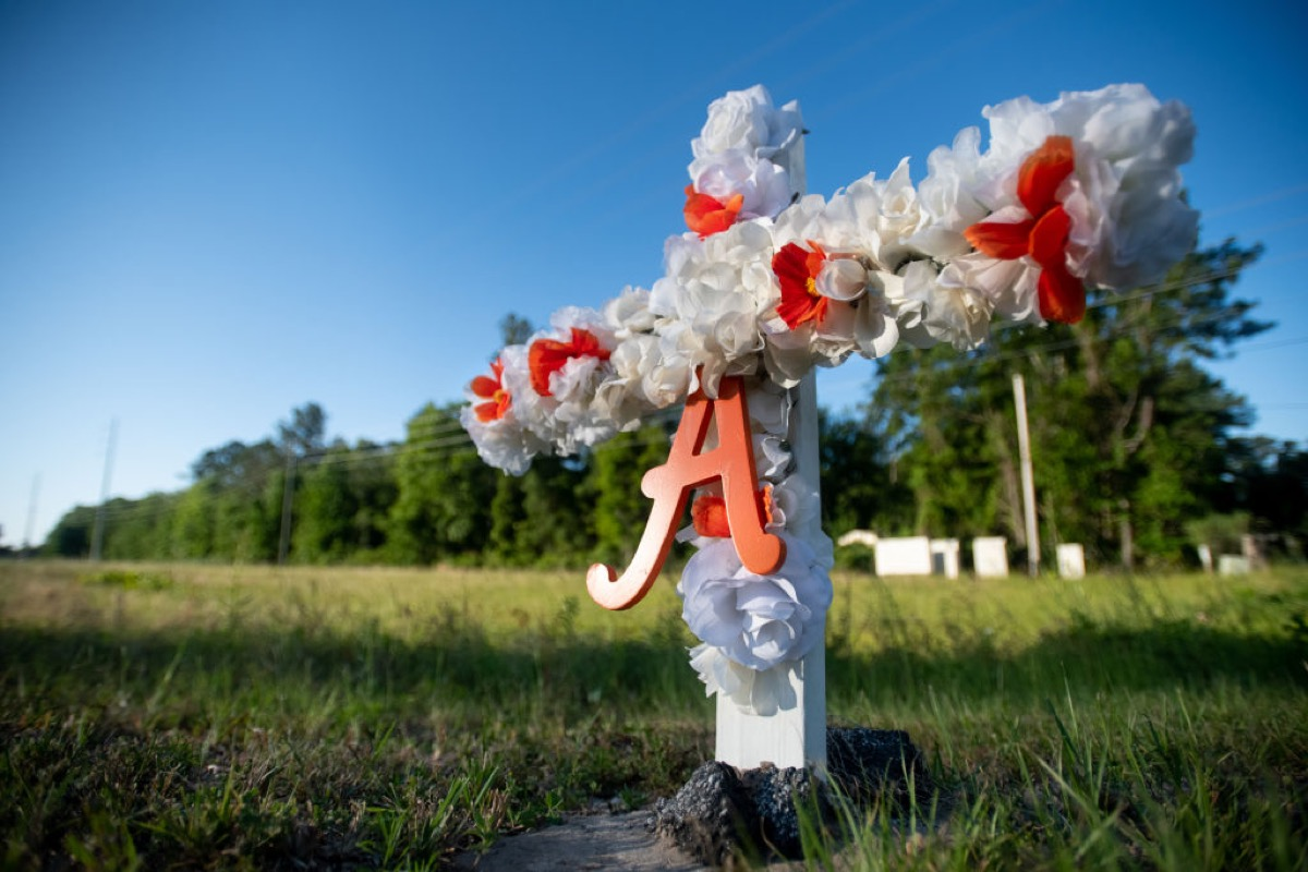 BRUNSWICK, GA - MAY 07: A cross with flowers and a letter A sits at the entrance to the Satilla Shores neighborhood where Ahmaud Arbery was shot and killed  May 7, 2020 in Brunswick, Georgia. Arbery was shot during  a confrontation with an armed father and son on Feb 23. (Photo by Sean Rayford/Getty Images)