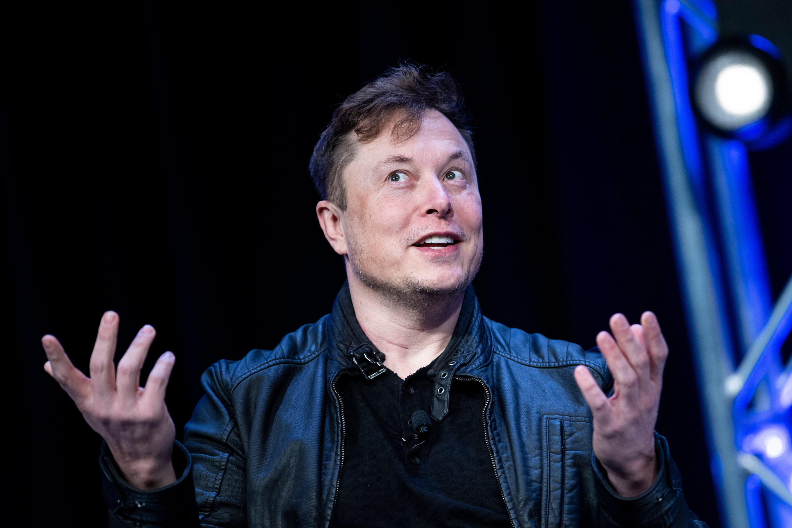 Elon Musk speaks and gestures in front of a black background