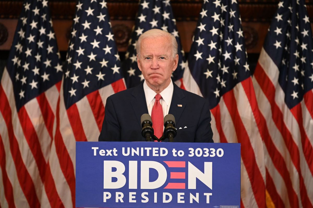 Joe Biden stands at a podium in front of American flags.