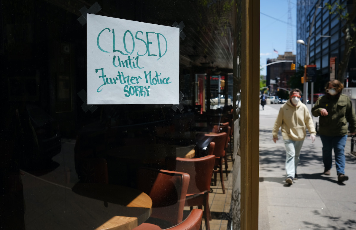 People walk through a shuttered business district