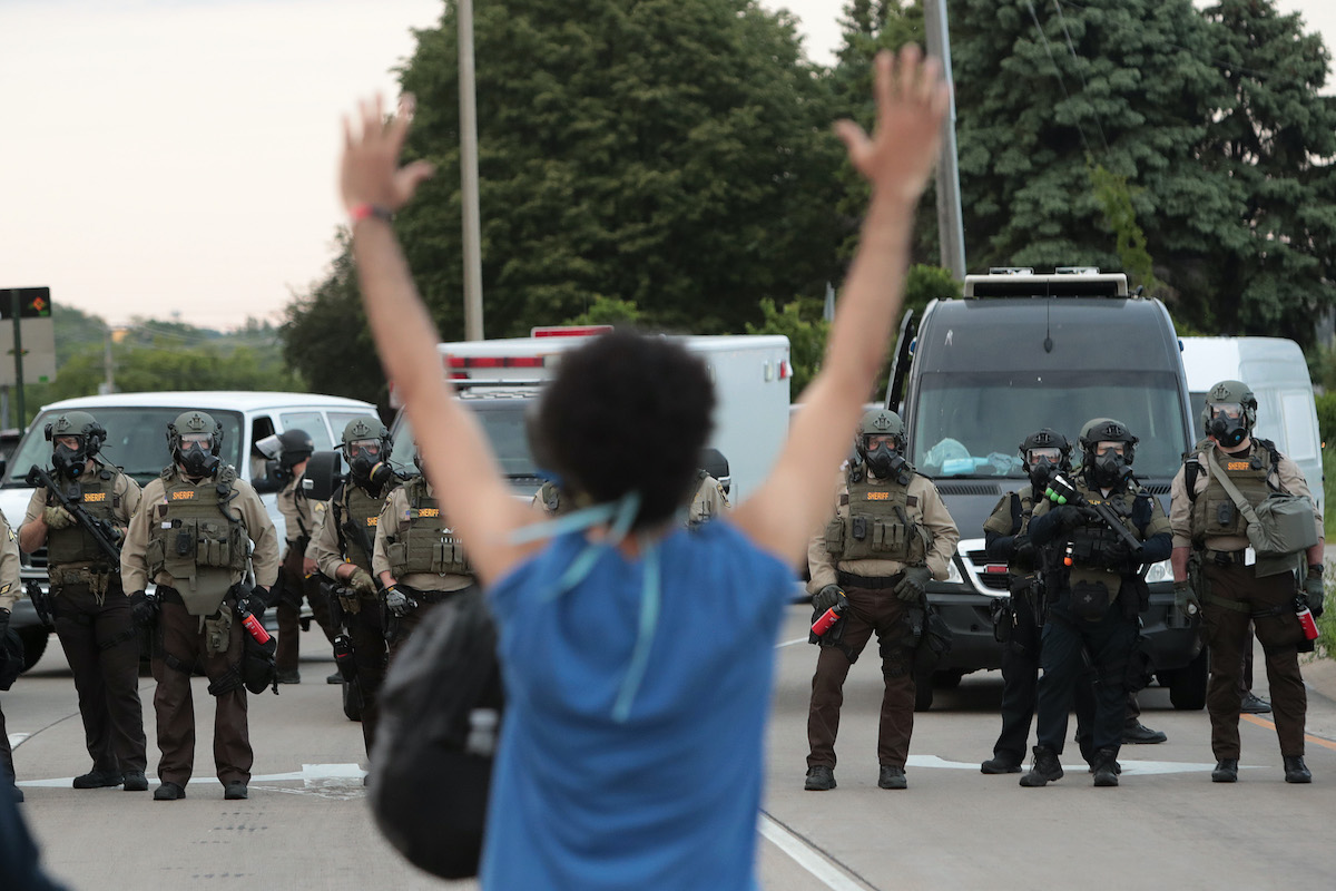 A demonstrator holds her hands up in front of police while protesting against the death of George Floyd