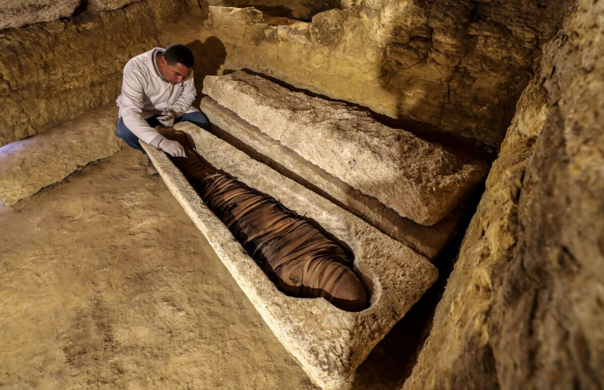 An Egyptian archeologist inspects a mummy in a limestone sarcophagus discovered along many finds in 3000-year-old communal tombs dedicated to high priests, in Al-Ghoreifa in Tuna al-Jabal in the Minya governorate, on January 30, 2020. - Egypt's antiquities ministry unveiled 16 tombs of ancient high priests containing 20 sarcophagi, including one dedicated to the sky god Horus, discovered at the archaeological site, about 300 kilometres (186 miles) south of Cairo. The shared tombs were dedicated to high priests of the god Djehuty and senior officials, from the Late Period, the ministry said. (Photo by Mohamed el-Shahed / AFP) (Photo by MOHAMED EL-SHAHED/AFP via Getty Images)