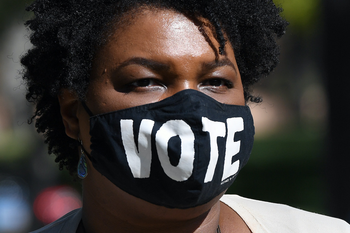 "Stacey Abrams wears a face mask reading ""VOTE"""