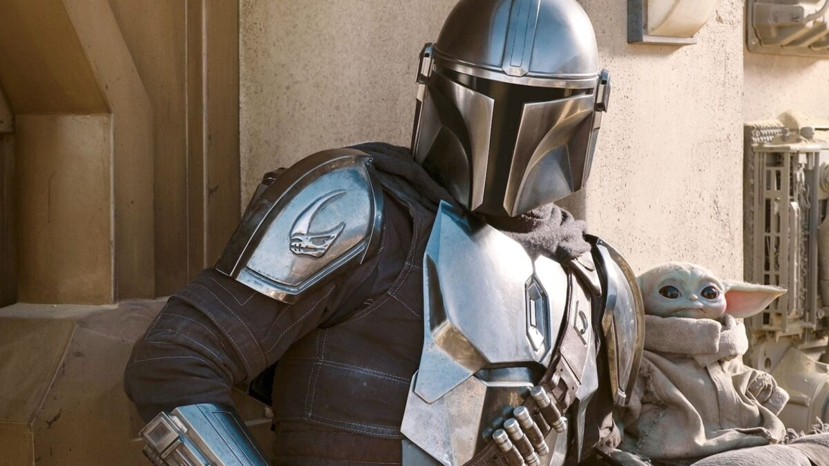 A man and his son (Din Djarin and Grogu) hanging out, on Disney+'s The Mandalorian Star Wars series.