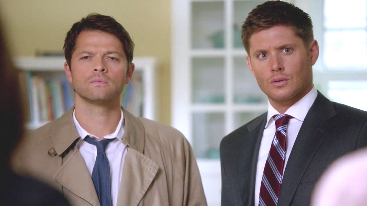 Castiel and Dean stand next to each other in The CW's Supernatural.