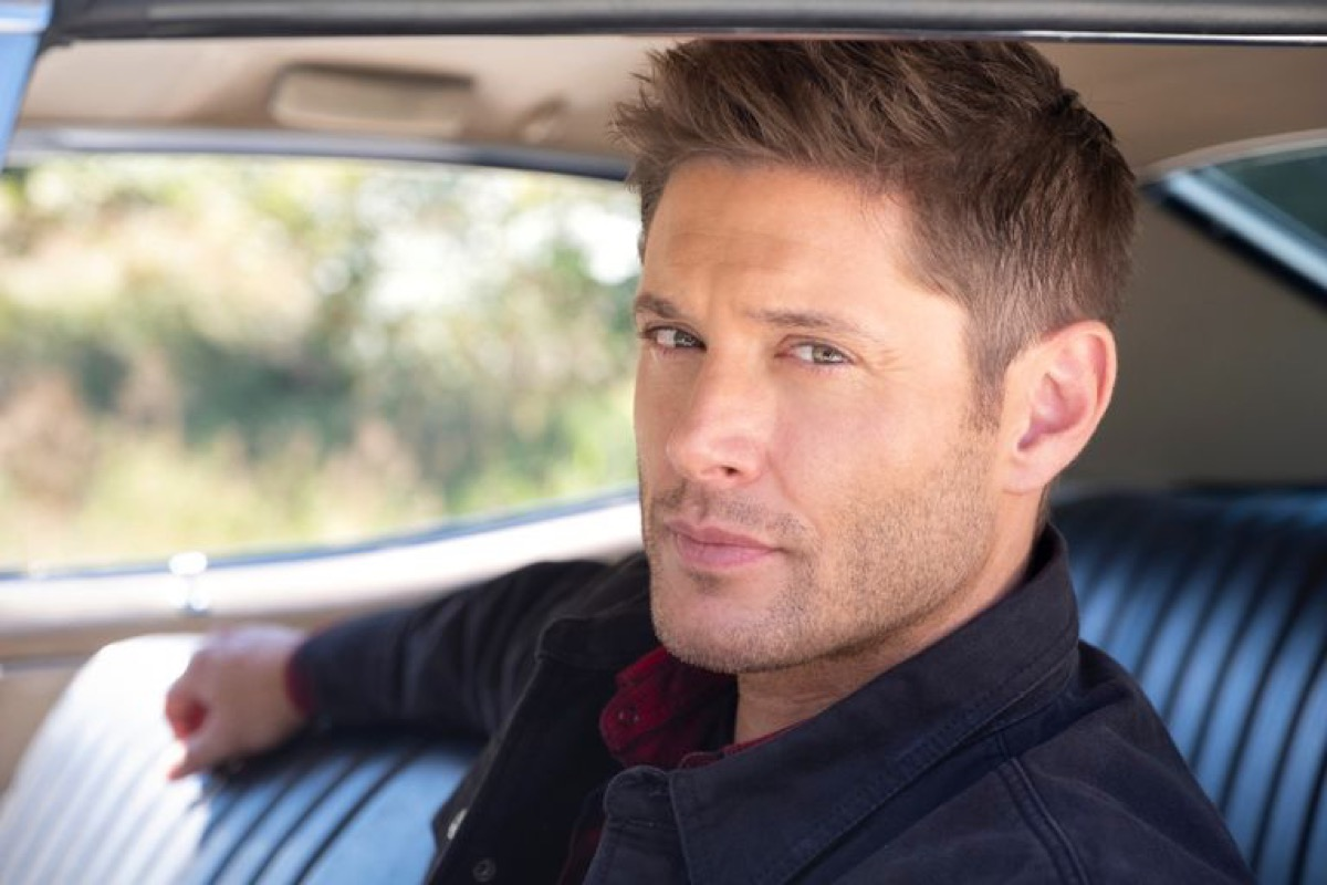 Dean Winchester sitting in the driver's seat of his car, smoldering at the camera in The CW's Supernatural finale.