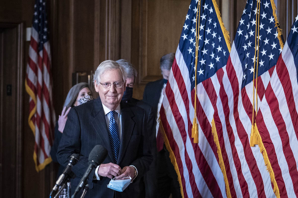 Mitch McConnell smirks as he enters for a press conference.