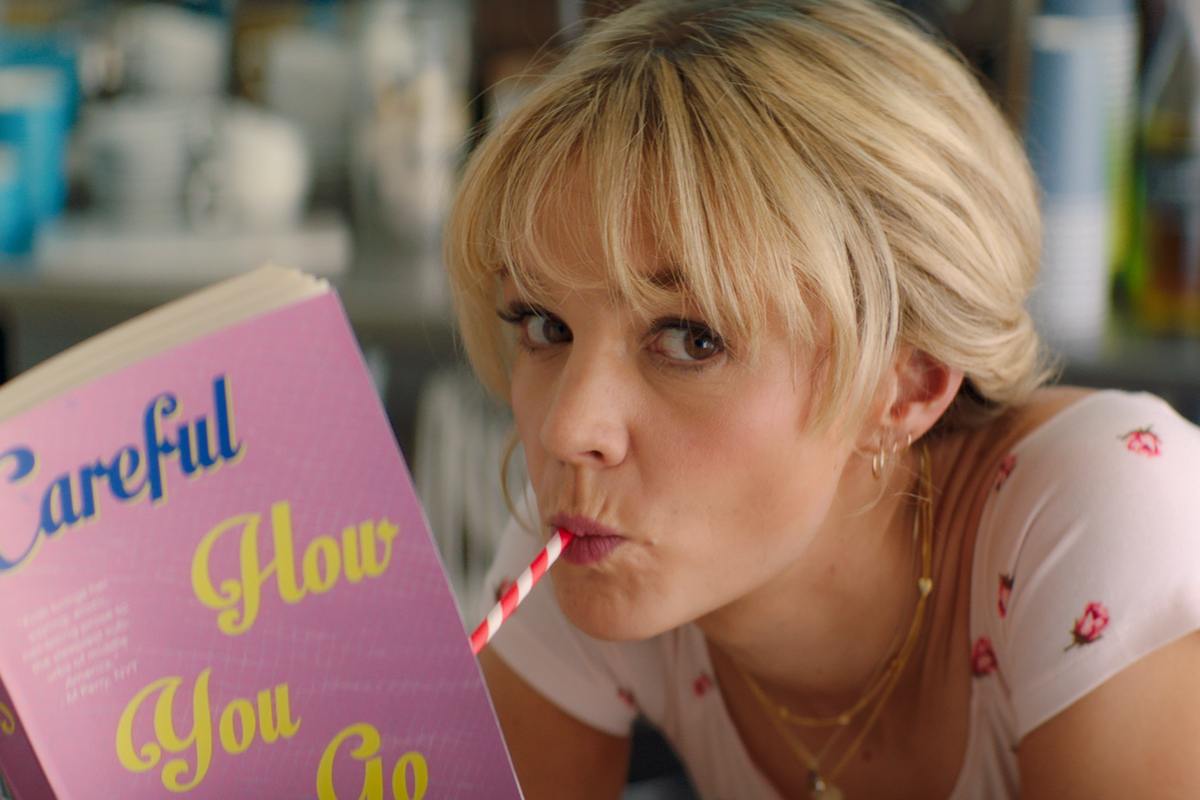In a scene from Promising Young Woman, Cassie (Carey Mulligan) drinks from a pink straw while reading a book with a pink cover.