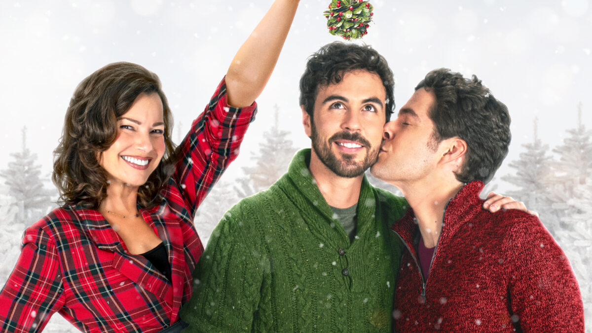 a mom holds mistletoe over her son and his boyfriend