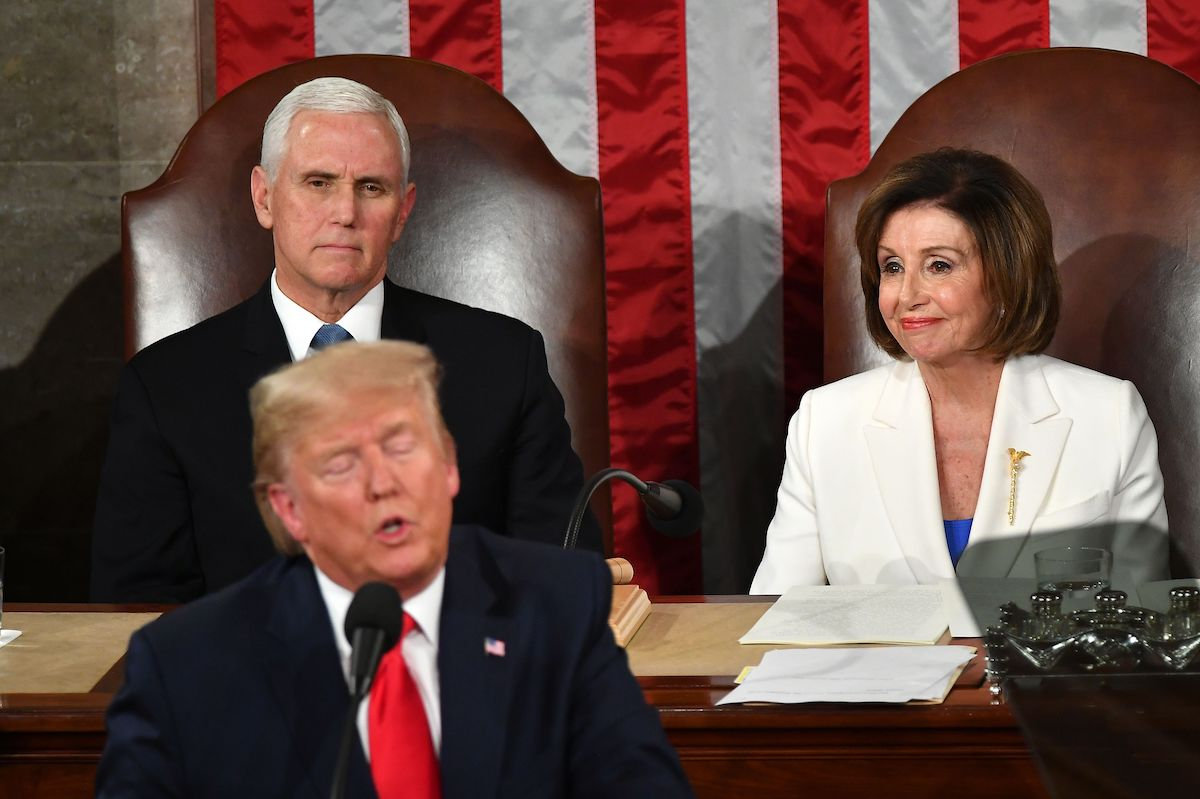 Nancy Pelosi sits next to Mike Pence, wearing her mace brooch while watching Trump give the state of the union address.